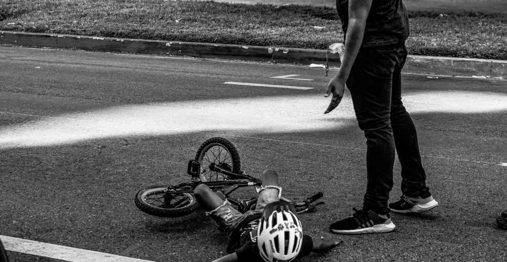 Father helping child who has fallen off his bike