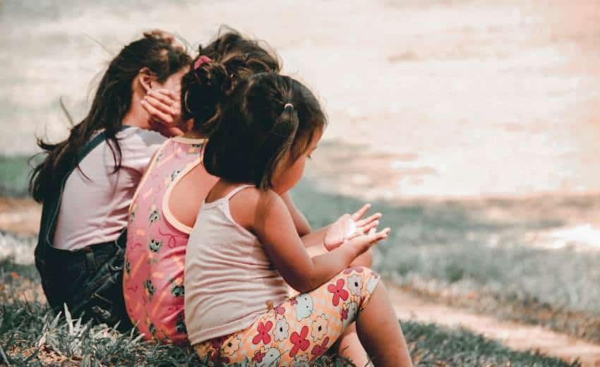 Kids sitting on grass.